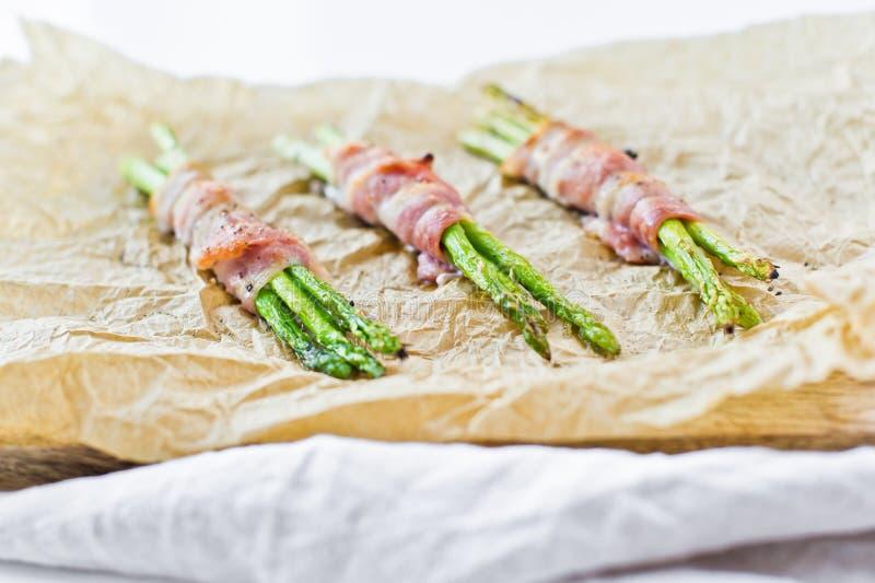 Organicznie zielony mini asparagus zawijaj?cy w bekonie na drewnianej tn?cej desce Bia?y t?o, odg?rny widok zdjęcia royalty free