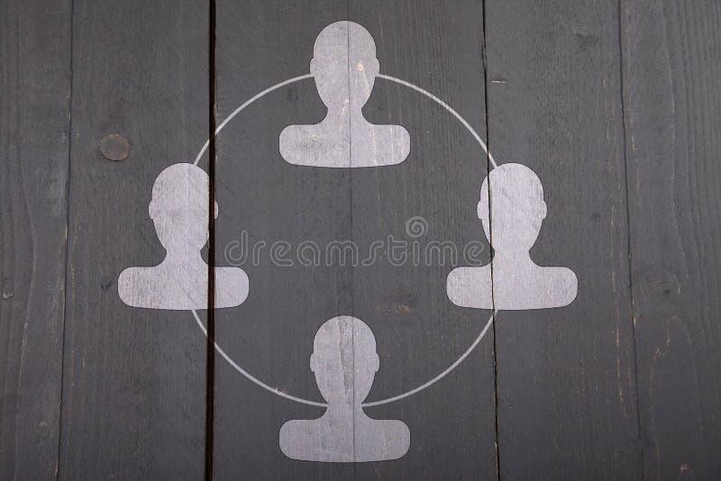 Organigrama blanco con las cabezas blancas en fondo de madera negro imagen de archivo