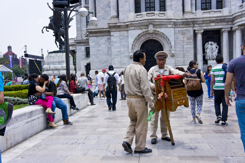 Organilleros. Two street organ players talking while tourists pass by in Mexico City stock photos
