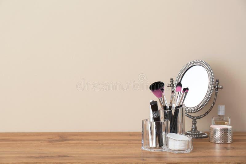 Organisateur avec les produits cosmétiques de maquillage et miroir sur la table contre le mur léger photos libres de droits