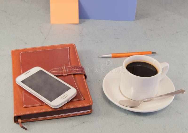 Organisateur de Brown, tasse de café blanc, téléphone portable, fond gris photographie stock libre de droits