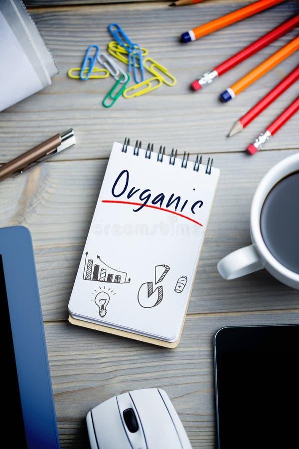 Organisch gegen Notizblock auf Schreibtisch stockbilder