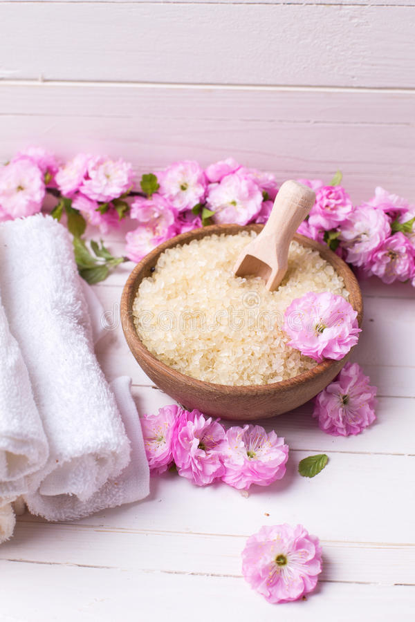 Organisch overzees zout in kom met handdoeken en roze bloemen stock afbeeldingen
