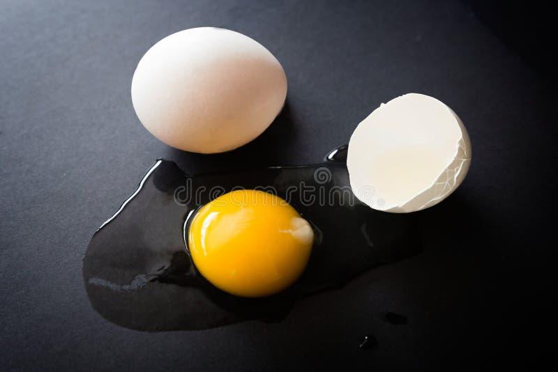 Organisch ruw gebarsten ei open op zwarte achtergrond stock foto's