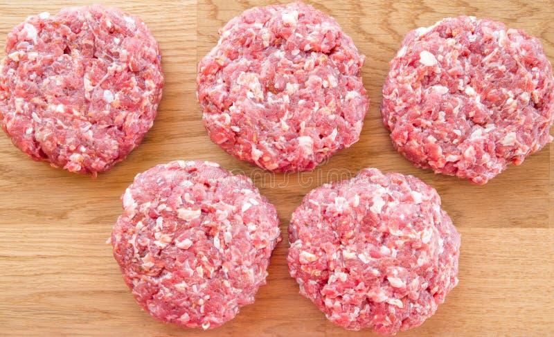 Organisch ruw rundergehakt, ronde pasteitjes voor het maken van eigengemaakte hamburger op houten scherpe raad royalty-vrije stock foto's