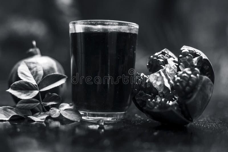 Organisch uittreksel van granaatappel met ruwe granaatappel op houten oppervlakte in een transparant glas stock afbeelding