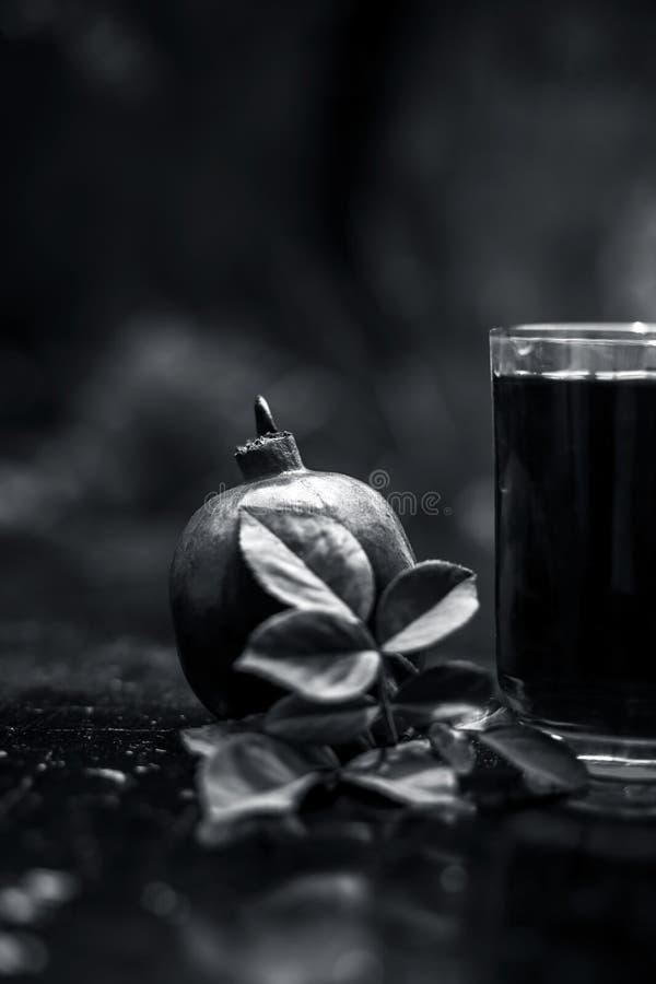 Organisch uittreksel van granaatappel met ruwe granaatappel op houten oppervlakte in een transparant glas royalty-vrije stock fotografie
