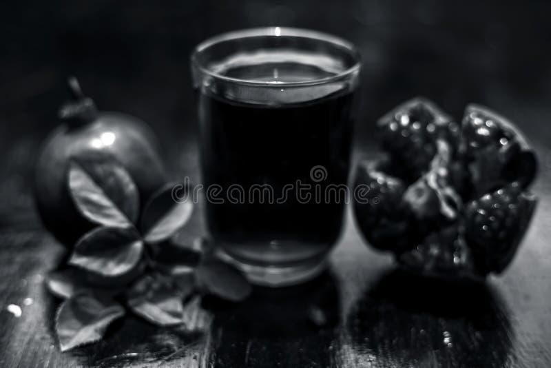 Organisch uittreksel van granaatappel met ruwe granaatappel op houten oppervlakte in een transparant glas stock foto