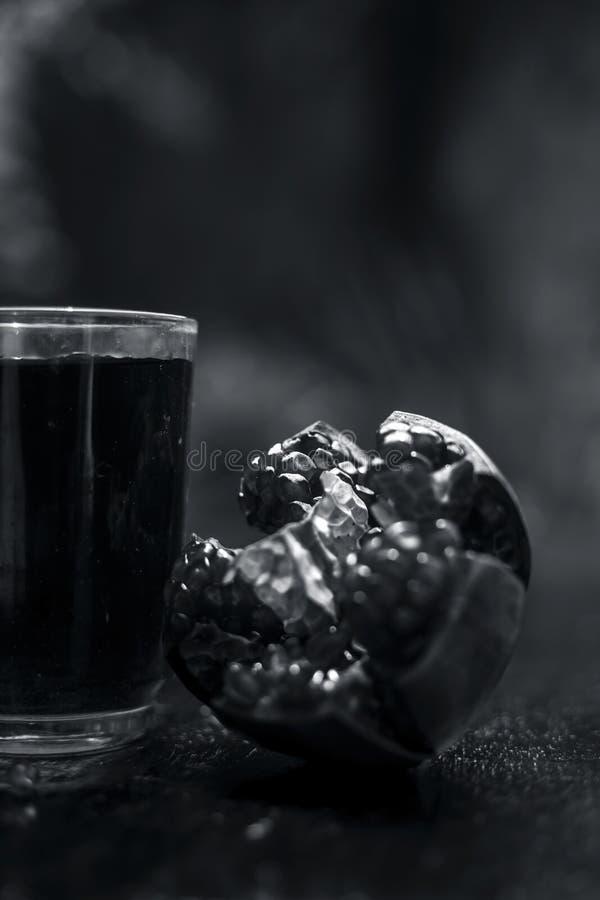 Organisch uittreksel van granaatappel met ruwe granaatappel op houten oppervlakte in een transparant glas stock foto's