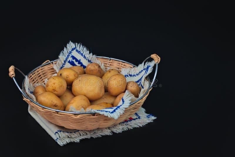 Organische aardappels in de mand op zwarte stock foto's