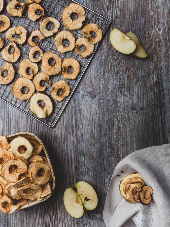 Organische appelchips (plakjes) op een houten achtergrond met kopieerruimte Gezonde vegetarische snack stock afbeelding