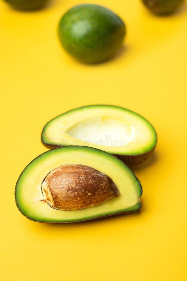 Organische avocado en zaad halve plak en geheel fruit op gele lijstachtergrond super voedsel keto voor dieet sluit omhoog de vers royalty-vrije stock afbeeldingen