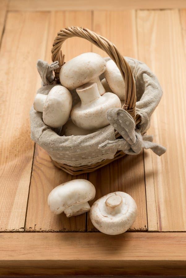 Organische Champignons in einem Weidenkorb auf einem hölzernen Hintergrund lizenzfreies stockfoto