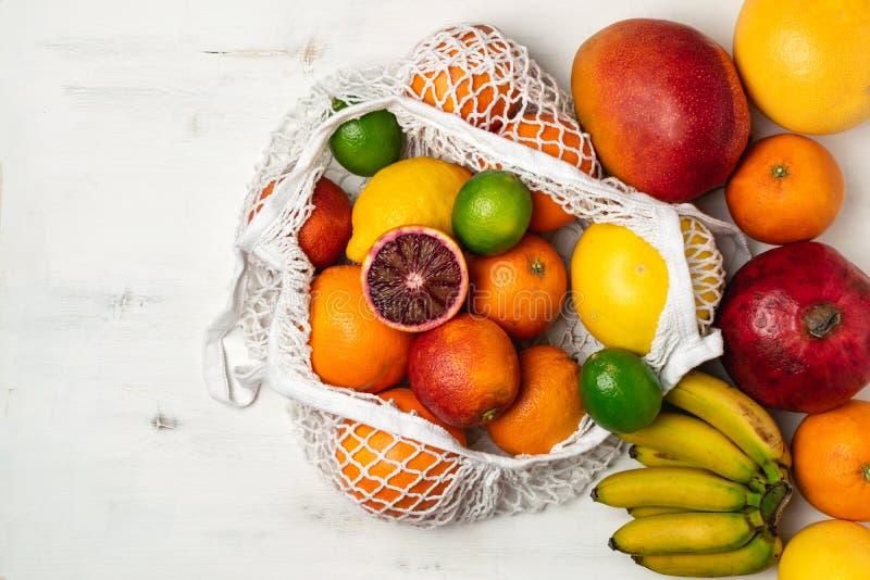 Organische citrusvruchtenverscheidenheid in het katoenen netwerk opnieuw te gebruiken winkelen zak - recycling, duurzame levensst stock foto
