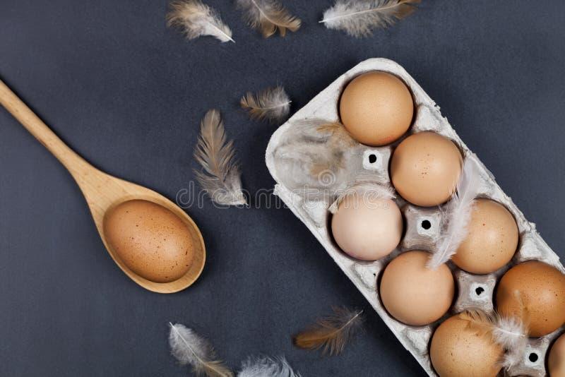 Organische eieren, houten lepel en veren stock afbeelding