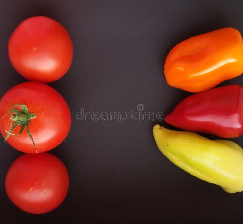 Organische, frische bunte Pfeffer und Tomaten auf schwarzer Tabelle stockfotos