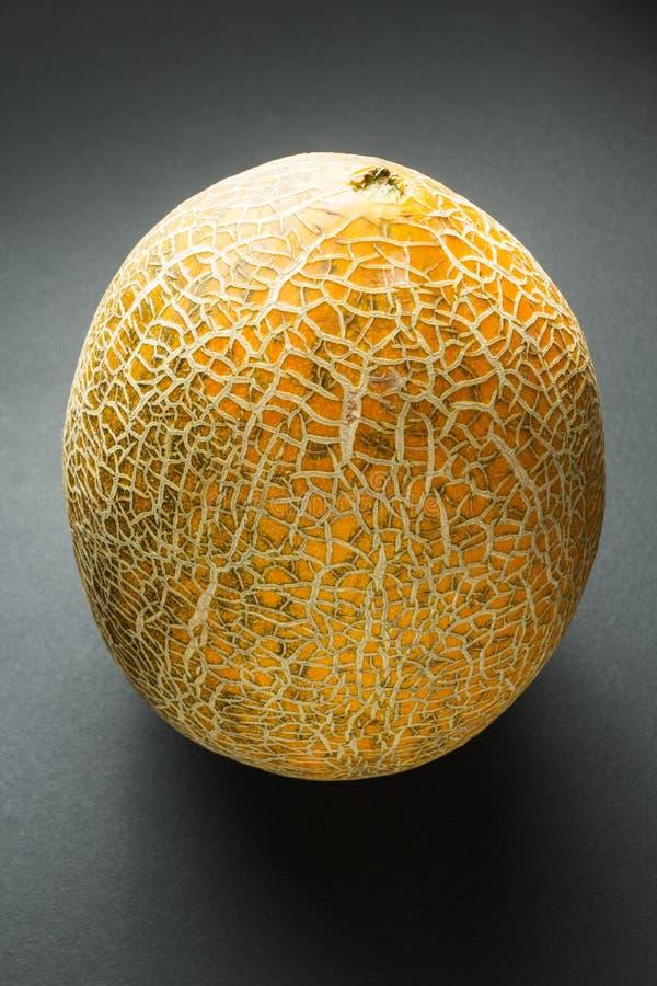 Organische frische Hami-Melone lokalisiert auf dem schwarzen Hintergrund, vertikal stockfotos