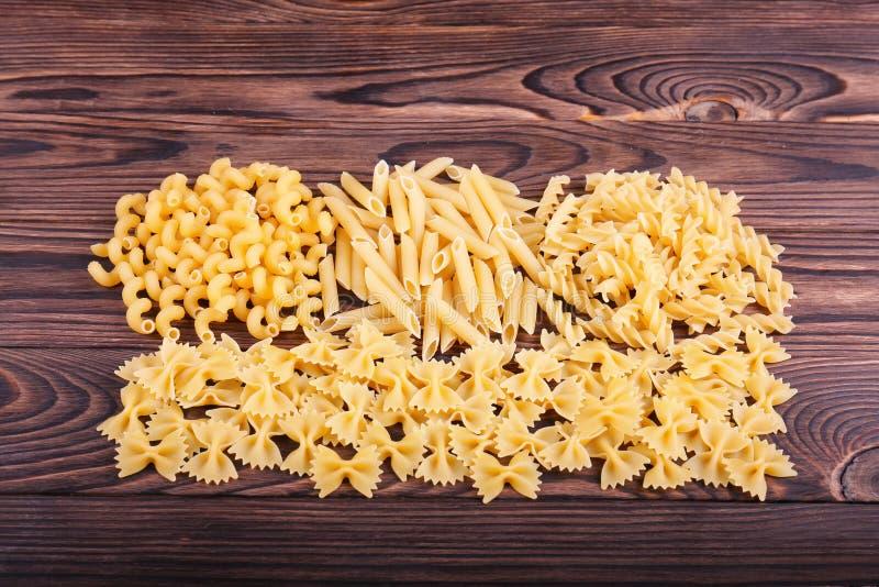 Organische gele rigatedeegwaren of macaroni op een donkere bruine houten achtergrond Droog, hard, ruw en helder geel concept royalty-vrije stock afbeelding