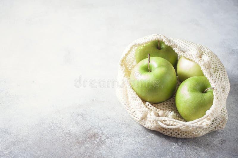 Organische groene appelen in opnieuw te gebruiken katoenen netto zak op houten lijst Eco-pakket, nul afvalconcept stock fotografie