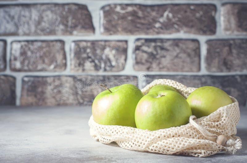 Organische groene appelen in opnieuw te gebruiken katoenen netto zak op houten lijst Eco-pakket, nul afvalconcept stock foto's