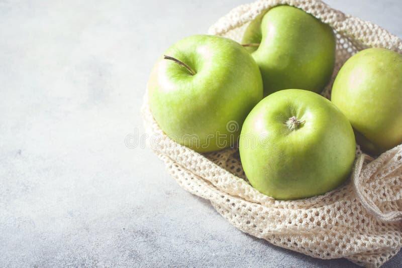 Organische groene appelen in opnieuw te gebruiken katoenen netto zak op houten lijst Eco-pakket, nul afvalconcept stock foto