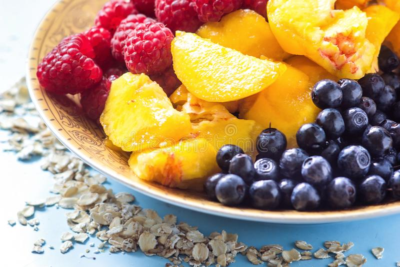 Organische havermeelhavermoutpap in witte ceramische kom met frambozen, perziken en bosbessen Gezond ontbijt - conc gezondheid en stock fotografie