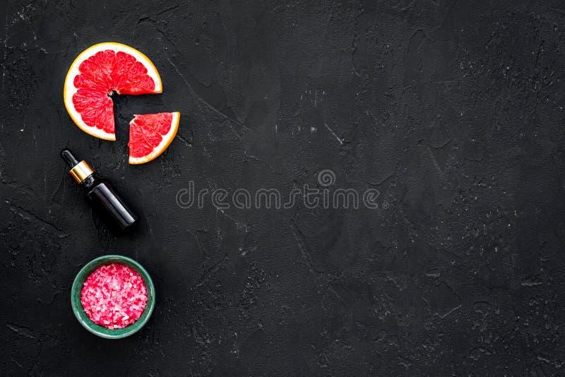 Organische Kosmetik mit Pampelmuse für selbst gemachten Badekurort mit Salz und frischer Frucht auf schwarzem Draufsichtmodell de stockfoto
