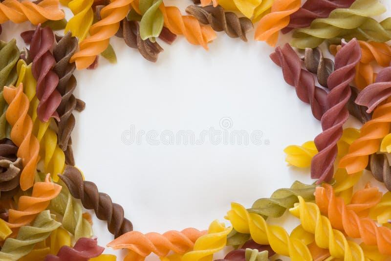 Organische multicolored spiraalvormige deegwaren voedsel multicolored achtergrond royalty-vrije stock fotografie