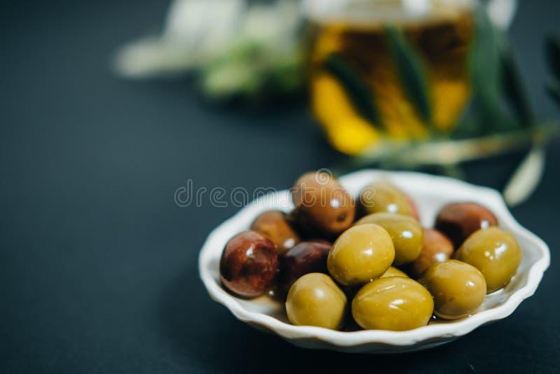 Organische Oliven, Öl und grüne Niederlassung auf schwarzem Hintergrund stockfotografie
