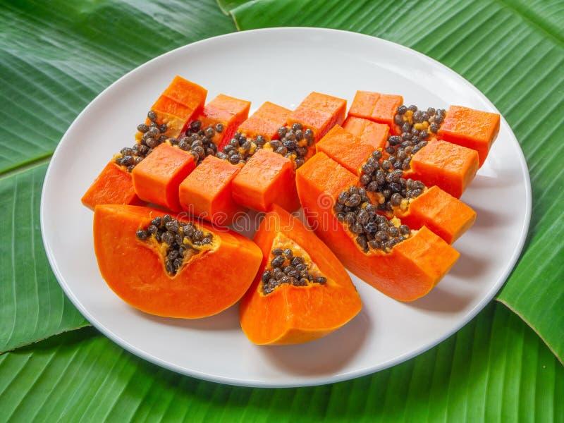 Organische papajastukken op witte plaat met de groene achtergrond van banaanbladeren Exotisch en tropisch fruit Vegetarische voed royalty-vrije stock foto