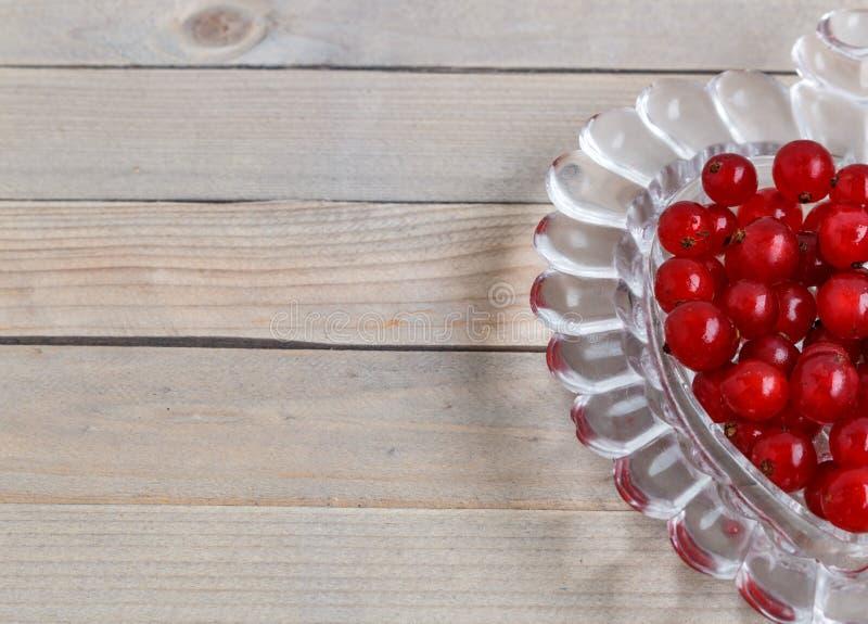 Organische tuinbessen op oude houten lijst, van hierboven Rode stroom kristalvaas in de vorm van hart stock afbeeldingen