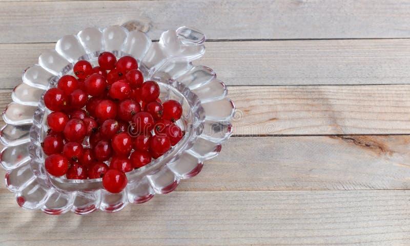 Organische tuinbessen op oude houten lijst, van hierboven Rode stroom kristalvaas in de vorm van hart stock foto's
