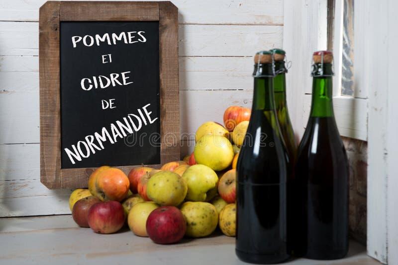 Organische verse appelen en fles de cider van Normandië met chalkboar royalty-vrije stock foto