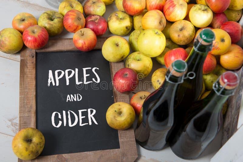 Organische verse appelen en fles de cider van Normandië met chalkboar stock afbeelding