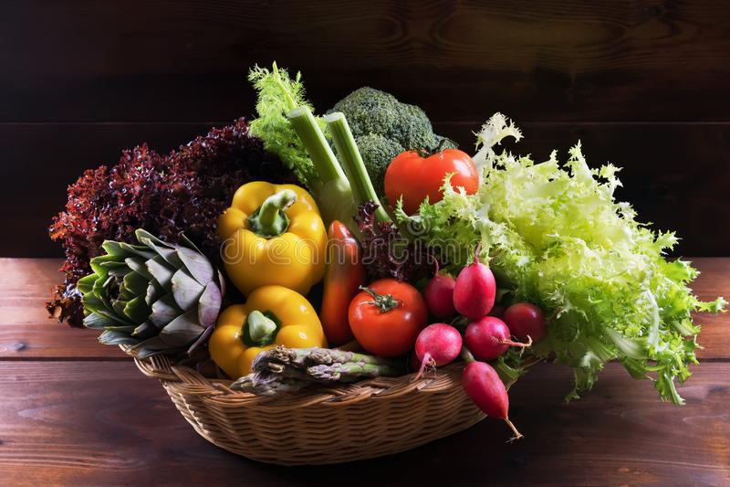 Organische verse groenten in mand op donkere houten achtergrond, gezond voedsel en schoon het eten concept stock fotografie