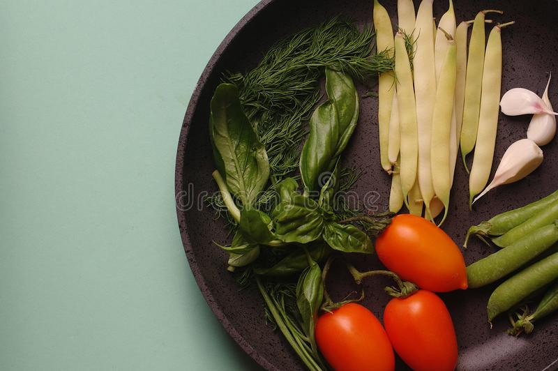 Organische verse groentencourgette, tomaat, asperge, basilicum, dille, groene erwten, knoflook in een pan stock afbeelding