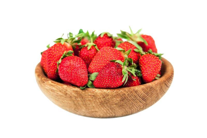 Organische verse rijpe aardbei in een houten die kom op een witte achtergrond wordt geïsoleerd Gezonde vruchten en bes, vegateria stock foto's
