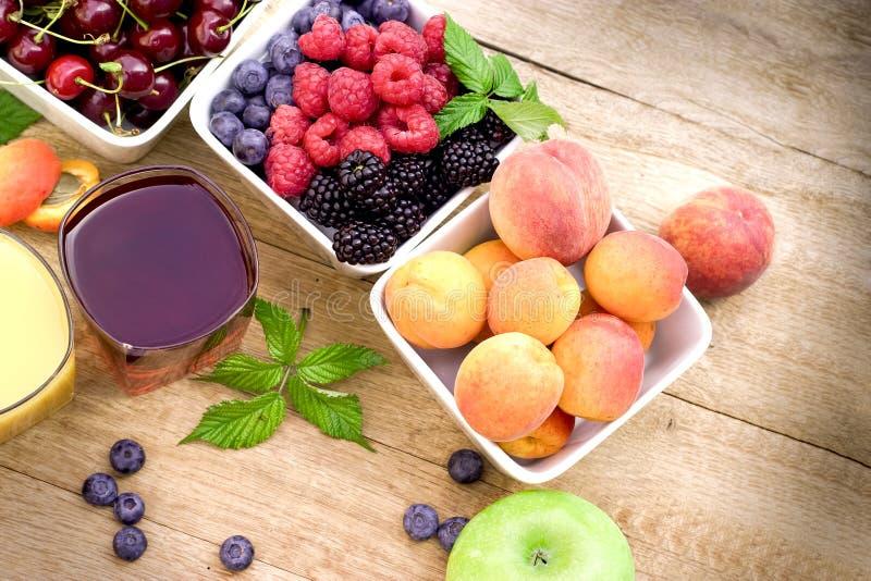 Organische vruchten en verse sappen op rustieke houten lijst royalty-vrije stock foto