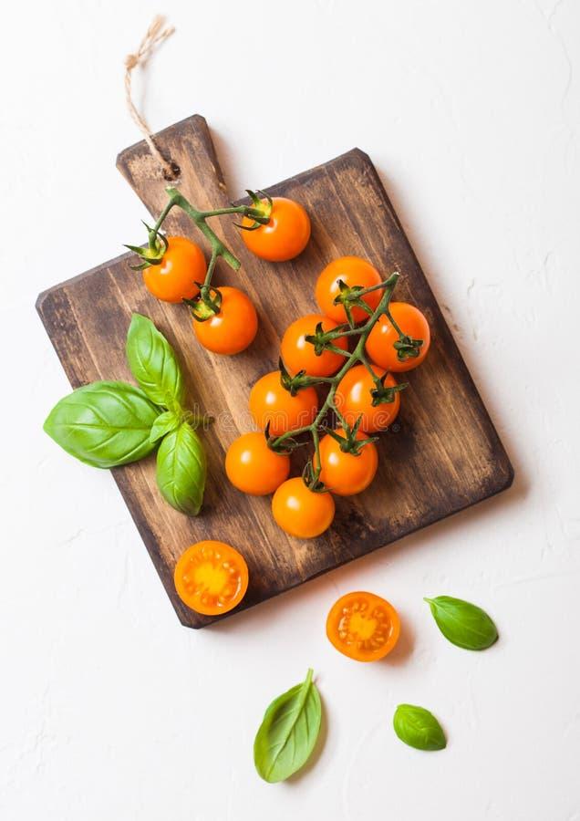 Organischer Cherry Orange Rapture Tomatoes auf der Rebe mit Basilikum auf hackendem Brett auf weißem Küchenhintergrund stockfotos