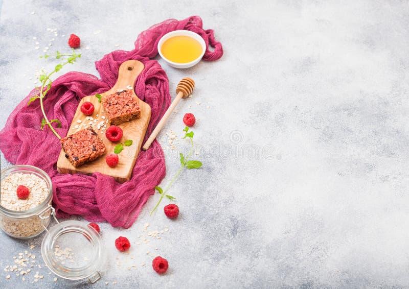 Organischer Getreidefruchtmüsliriegel mit Beeren auf Weinlesebrett mit Honiglöffel und Glas Hafern auf purpurrotem Stoff Erdbeere stockfoto