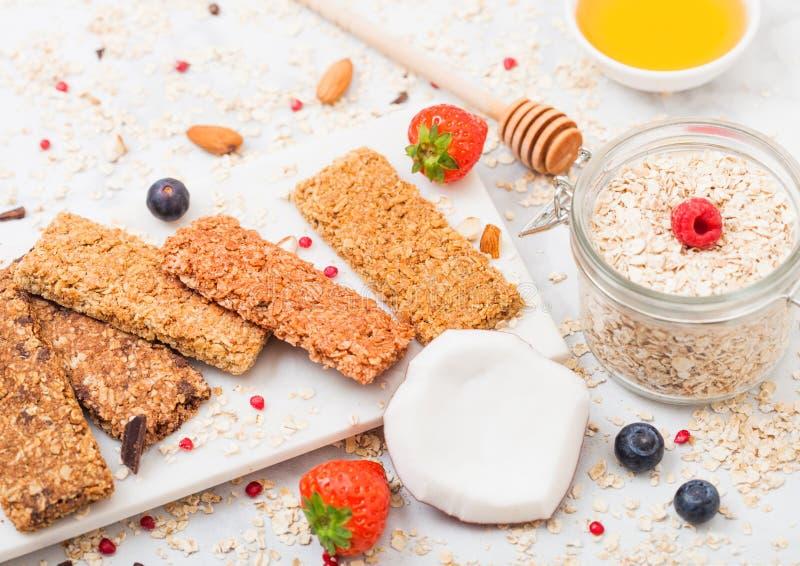 Organischer Getreidemüsliriegel mit Beeren auf Marmorbrett mit Honiglöffel und Glas von Hafern und von Kokosnuss auf Marmorhinter stockfotografie