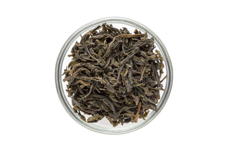 Organischer grüner Tee (Kamelie sinensis) trocknete lange Blätter in der Glasschüssel stockfoto