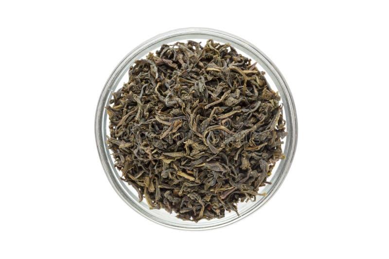 Organischer grüner Tee (Kamelie sinensis) trocknete lange Blätter in der Glasschüssel stockfotos