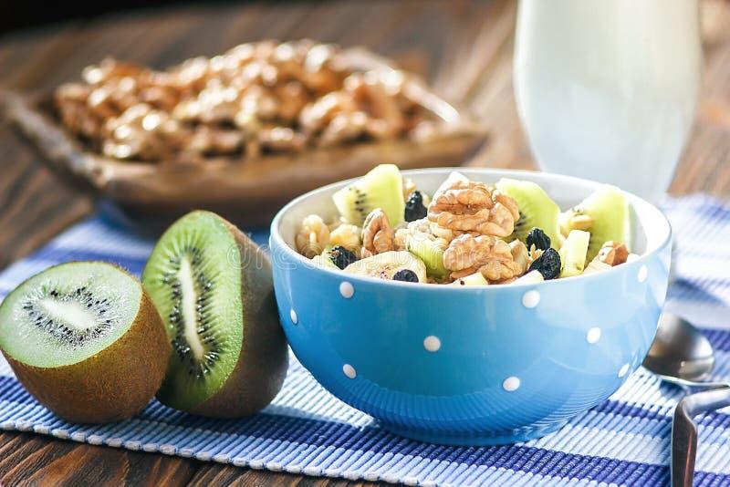 Organischer Hafermehlbrei in der keramischen Schüssel mit Bananen, Honig, Walnüssen, Kiwi und Rosinen Gesundes Frühstück lizenzfreies stockfoto