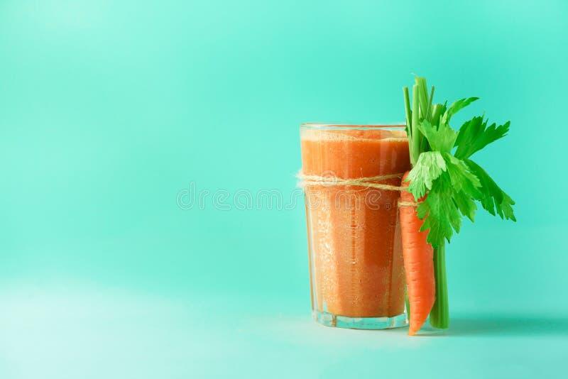 Organischer Karottensaft mit Karotten, Sellerie auf blauem Hintergrund Frischgemüse smothie im Glas fahne Kopieren Sie Platz stockbilder