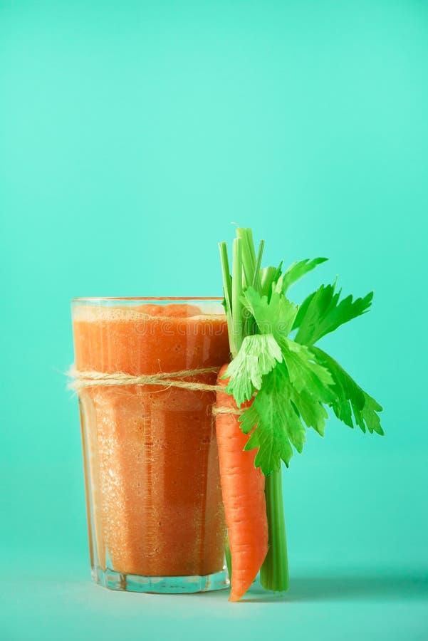 Organischer Karottensaft mit Karotten, Sellerie auf blauem Hintergrund Frischgemüse smothie im Glas fahne Kopieren Sie Platz lizenzfreie stockfotos