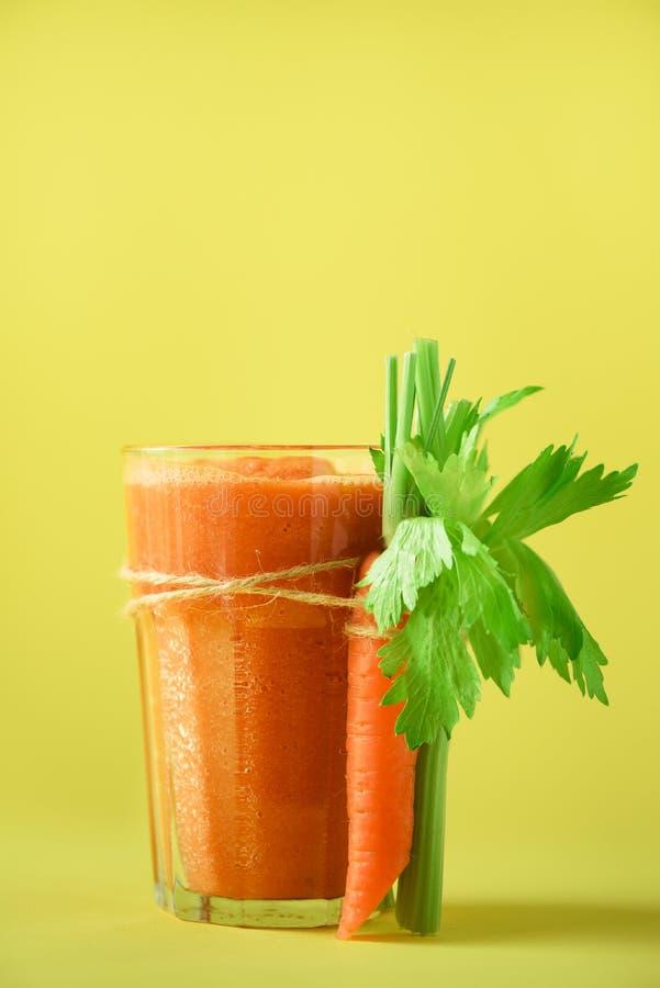 Organischer Karottensaft mit Karotten, Sellerie auf gelbem Hintergrund Frischgemüse smothie im Glas Kopieren Sie Platz Sommer stockbild