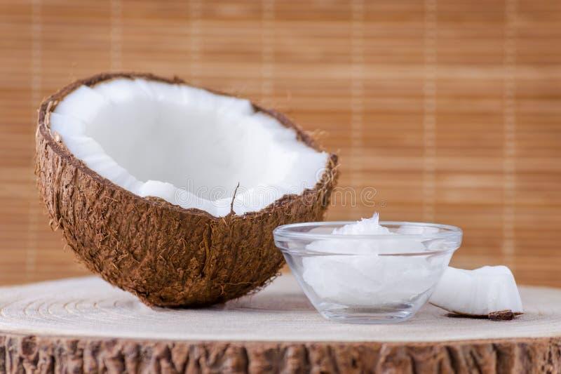 Organischer Kokosnussöl in einer Glasschüssel und in einer Kokosnuss auf natürlichem braunem Hintergrund stockfotografie