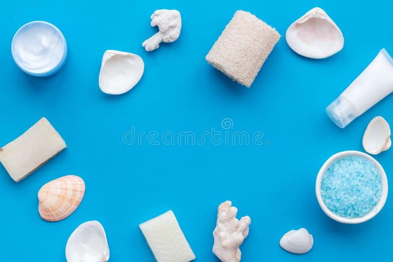Organischer kosmetischer Rahmen mit Salz, Creme und Lotion des Toten Meers auf blauem Draufsichtspott des Hintergrundes oben lizenzfreie stockfotografie