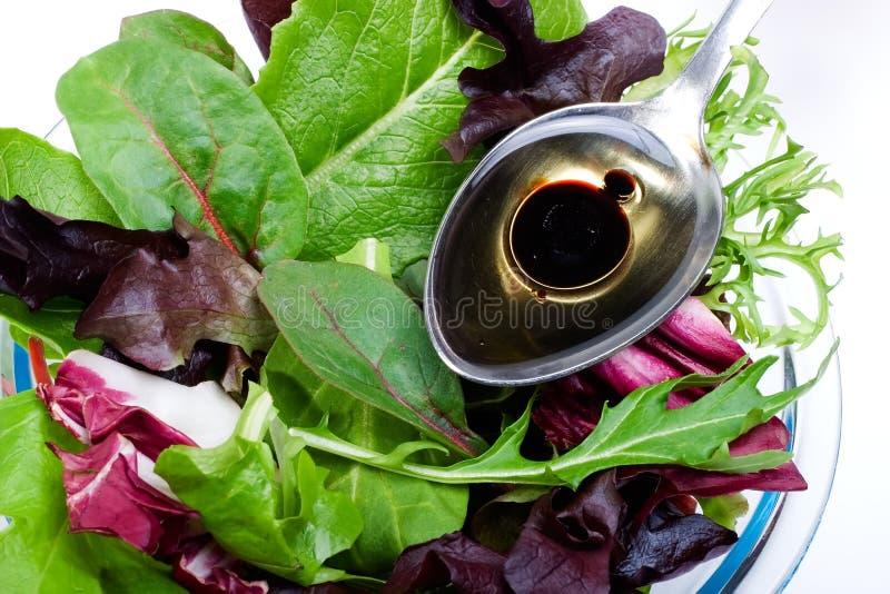 Organischer Salat und Löffel des Olivenöls stockfotos